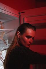 Side view of calm woman near the fridge