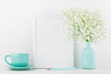 Mockup of picture frame decorated flowers in vase and coffee cup on white table with clean space for text and design your blogging.