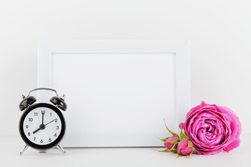 Mockup of picture frame decorated rose flower and alarm clock on white table with empty space for text and design your blogging.