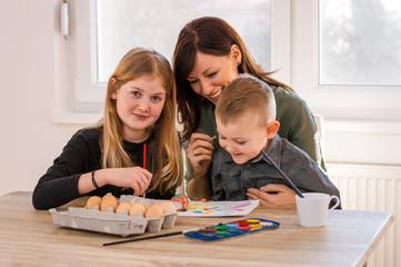 Mother and two children painting eggs