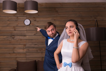 Bride talking by phone, groom showing on watch