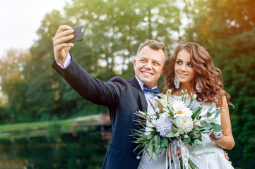 Beautiful happy husband and wife do selfie on wedding day