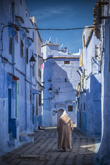 Man with a traditional dress is walking in the blue medina of Chefchaouen, Morocco.