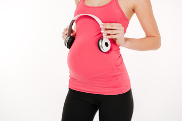 Cropped image of pregnant fitness woman holding headphone on tummy