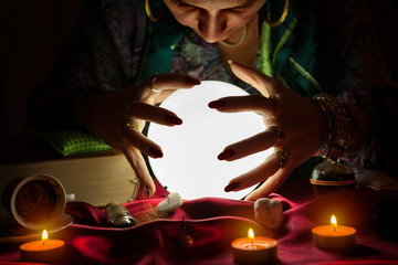 Woman fortune teller looking at crystal ball