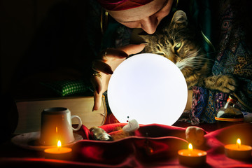Gypsy woman fortune teller holding cat in her arms