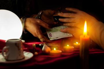 Fortune teller receive money for bottle of potion
