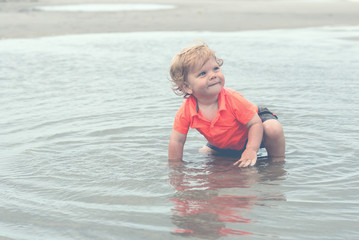 Smiling Child in Water on a Beach