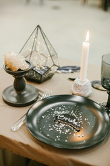 Wedding tableware with name card, stone candlestick with candle and other elements of festive table wedding centerpieces decorations.