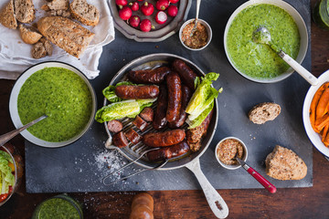 Dinner table with green soup creamy and grilled sausages and variety green veggies. Top view.