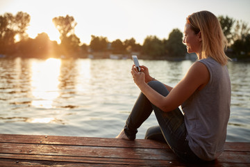 Woman with cellphone by river