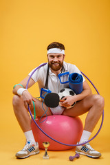 Happy cheerful fitness man sitting on a sports ball