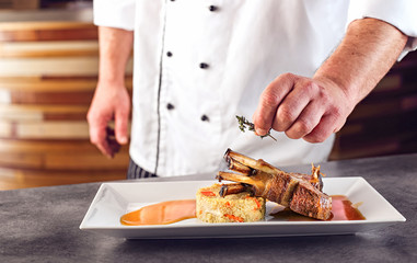 Chef in hotel or restaurant kitchen cooking only hands. Lamb chop preparation,decor in the kitchen.