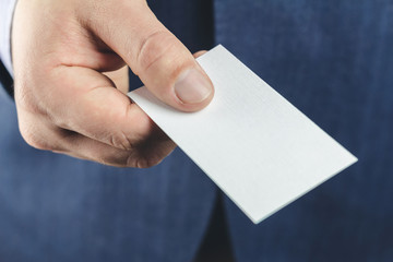 Close-up of business man in blue suit holds white blank business card in the hand.