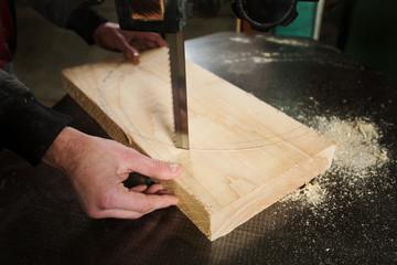 A carpenter cuts a piece of wood to the machine