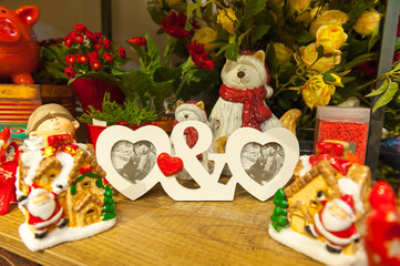 Heart shaped photo frame on wood table Against the background of Christmas toys