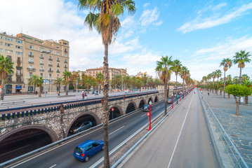 Late afternoon in Seaside Barcelona, Spain, sees traffic in tunnelled streets and pedestrian traffic above as people enjoy walking outdoors along the waterfront in warm weather in November.