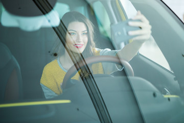 Smiling young woman taking selfie picture with smart phone camera in car