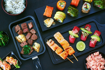 Top view of grilled salmon on skewers, sliced beef steak in a pan, variety of sushi rolls on board, tuna sushi, crab meat, wakame salad and bowl of steamed rice. Gourmet asian dinner concept.
