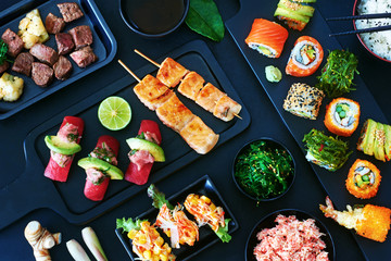 Top view of japanese style meal over dark background. Tuna sushi, assorted sushi rolls with salmon, avocado, crab, slice beef steak, wakame, crab salad and green tea.
