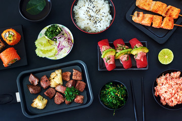 Top view of tuna sushi, sliced beef steak in a pan, grilled salmon on a skewers, bowl of steamed rice, crab meat and wakame salad on a black table. Gourmet japanese meal concept.