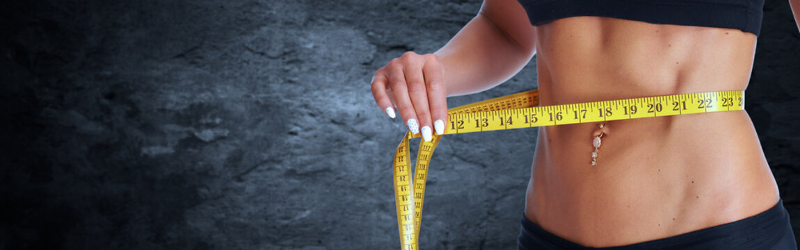 Woman waist with measuring tape over gray background.