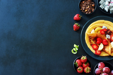 Healthy breakfast with homemade crepes with strawberries, grapes, dragon fruit, golden kiwi and honey over black background with a copy space.