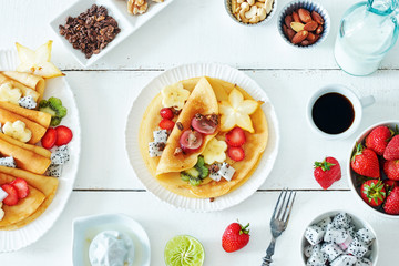 Top view of thin pancakes with starfruit, banana, kiwi, grape, strawberry and honey. Milk and coffee on a white table. Healthy breakfast with crepes.
