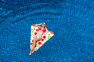 A beautiful bright funny woman is floating on an inflatable pizza in the pool, sunbathing, laughing. Rest on a tropical island. Perfect body and healthy skin, hair, fashionable bikini, view from above