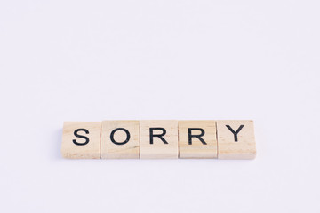 Text wooden blocks spelling the word sorry on white background