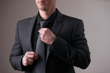 Close up portrait of stylish businessman in black trendy suit correcting tie and holds a hand in pocket isolated on white background.