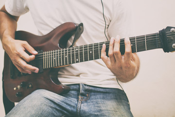 Handsome young asian men playing guitar and  listen music with headphones,Blurry and soft focus