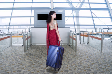 Woman with saree clothes and bag in airport