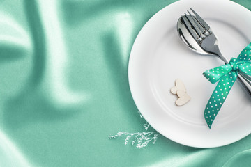 wooden heart shape with White empty plate with fork and spoon on pastel green silk fabric for love dinner concept
