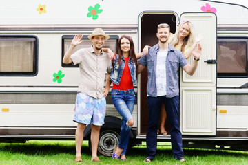 Happy friends are having a good time together in camper trailer. Holiday, vacation, trip concept.
