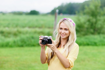 Attractive, beautiful, young girl taking pictures outdoors. Holiday, vacation, hobby concept.