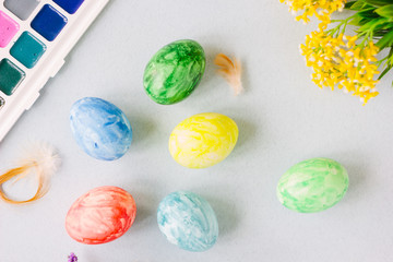 Easter composition - top view of colored eggs, paints, flowers and paint brush.