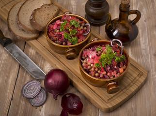Russian beetroot salad vinaigrette Keramiktopf on wood background