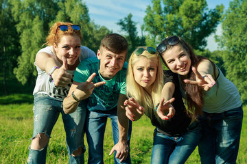 people, freedom, happiness, and teenage concept - group of happy friends go out and fun on a background of green trees