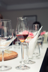 Marsala or madeira wine to the wine glass. Serving table prepared for event party or wedding. Soft focus, selective focus. Toned.
