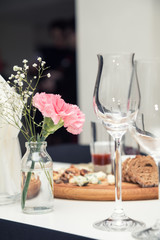 Close up picture of wine glasses with flower and empty glasses in restaurant. Serving table prepared for event party or wedding. Soft focus, selective focus. Toned.