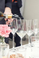 Sommelier pouring white wine to the wine glass. Serving table prepared for event party or wedding. Soft focus, selective focus. Toned.