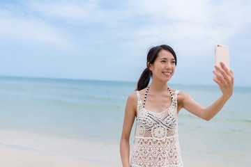 Woman taking selfie by mobile phone with the sea