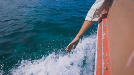 Woman waving her hand over the sea waves during motion of the boat. On board the old motorboat peeled off paint.
