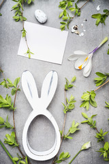 Easter greeting with blank white card , eggs, spring twigs , flowers and bunny decor, top view