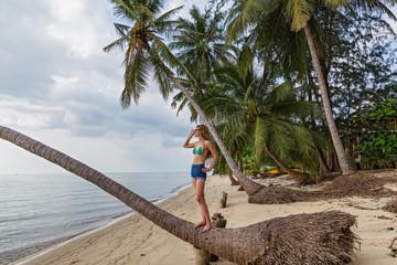 Woman  on a fallen palm tree