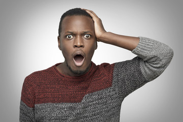Portrain of terrified young African American man in casual sweater. holding hand on his head and screaming with horrified look, opening mouth widely. Black male feeling scared or stressed. OMG concept