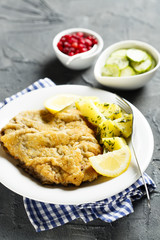 Classic schnitzel with lemon, potato, cucumber salad and berries