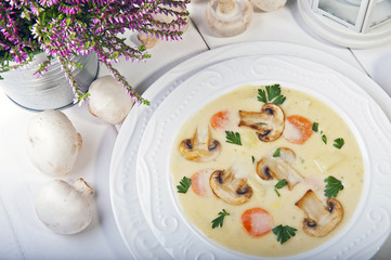 Champignon soup with parsley, carrots and potatoes on a white wooden table