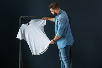 Hipster man dressed in denim shirt, stands indoors against background of dark wall and looks at white T-shirt